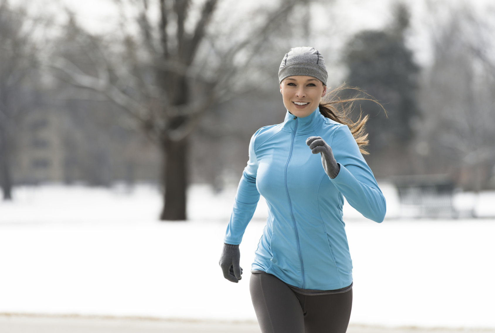 Young Woman Running in Snowy Park