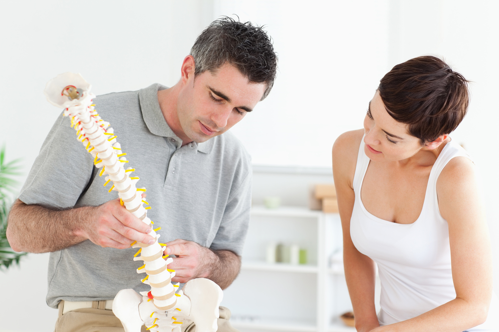 Chiropractic Care | chiropractor showing patient spine