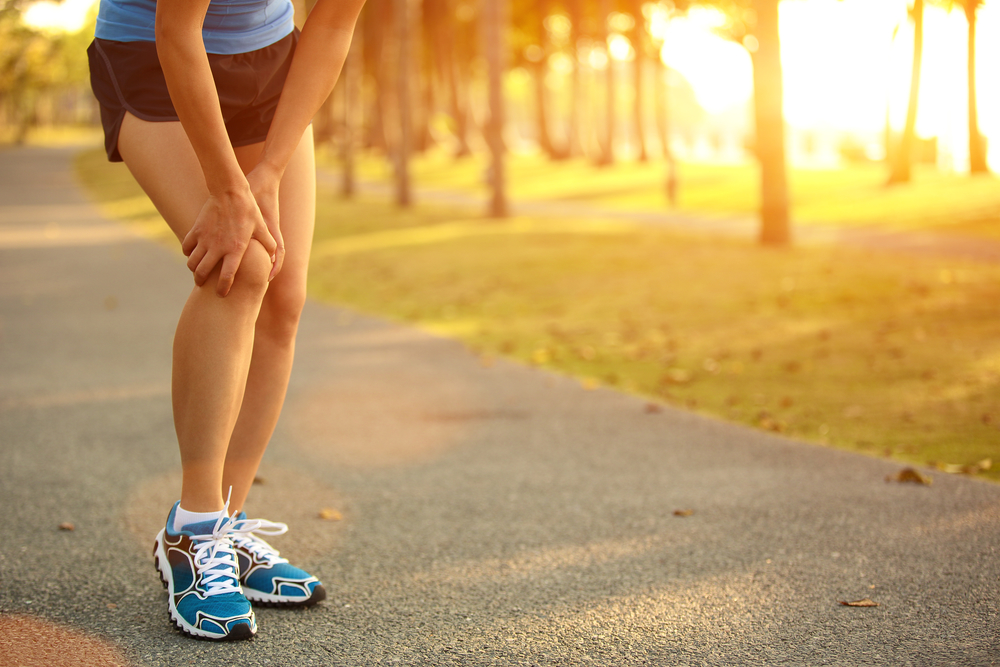 IT Band Syndrome | female runner holding injured leg
